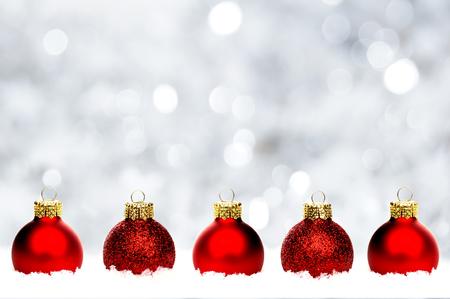 hilera: Frontera de la Navidad de bolas de color rojo brillante de descanso en la nieve con un abrir y cerrar de plata de fondo