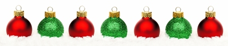 Christmas border of shiny red and green baubles resting in snow over a white background