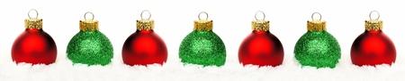 hilera: Frontera de la Navidad de brillantes bolas de color rojo y verde de descanso en la nieve sobre un fondo blanco Foto de archivo