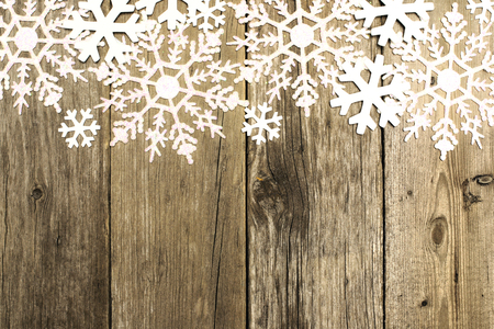 wood panel: Grunge wood Christmas background with shiny snowflake top border Stock Photo