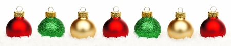 group of christmas baubles: Christmas border of shiny red gold and green baubles resting in snow over a white background Stock Photo