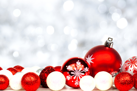 Christmas border of red and white ornaments over a twinkling silver light background photo