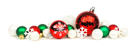 Christmas border of red, green and white ornaments over a white background