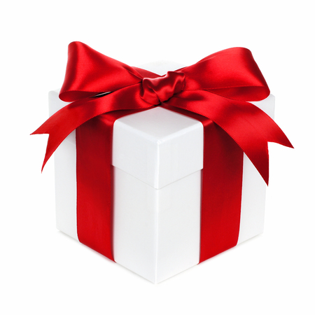 traditional gifts: Single white Christmas gift box with red bow and ribbon isolated on white