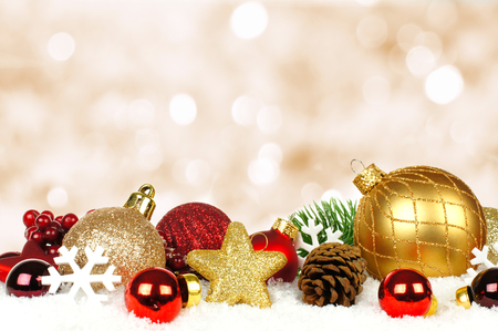 holiday lights display: Gold and red Christmas ornament border in snow with twinkling gold light background Stock Photo