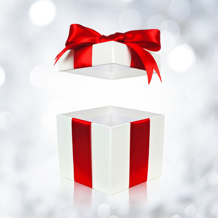 Open red and white gift box with floating lid on twinkling silver light background