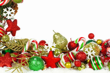group of christmas baubles: Christmas corner border of branches with red and green ornaments in snow Stock Photo