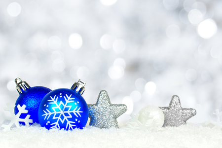 Christmas border of blue and silver ornaments in snow with twinkling light background photo