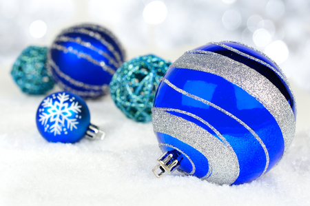 Blue Christmas ornaments in snow with twinkling silver lights background Stock Photo