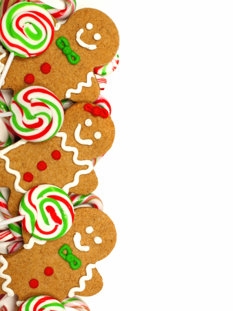 Christmas border of colorful gingerbread men and candies over a white background