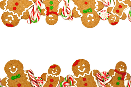 Christmas frame of colorful gingerbread men and candies over a white background photo