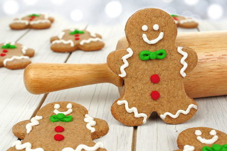 Christmas gingerbread men with rolling pin on a white wood background photo