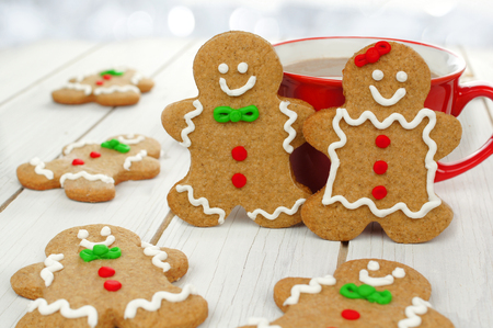 Christmas gingerbread couple with hot chocolate on a white wood background photo