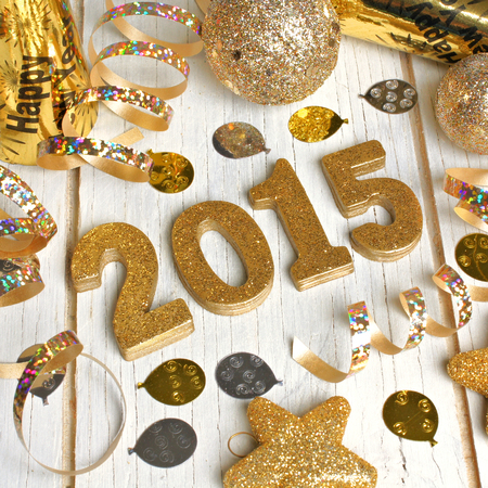 new years: 2015 New Years Eve golden numbers with confetti and decorations on a white wood background Stock Photo