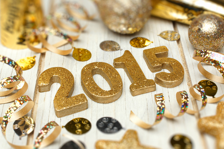 shiny background: 2015 New Years Eve golden numbers with confetti and decorations on a white wood background Stock Photo
