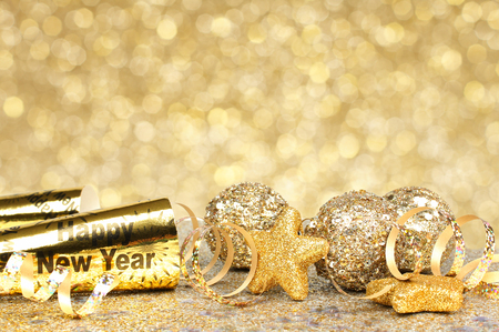 New Years Eve border of confetti and golden decorations on a twinkling gold background Imagens - 33897524