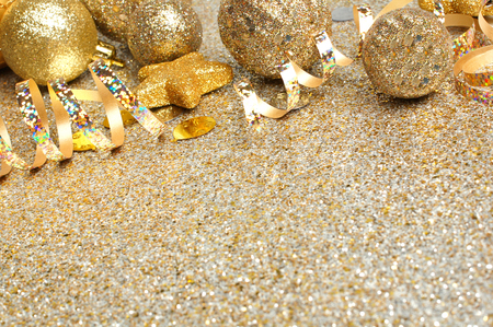 New Years Eve border of confetti and golden decorations on a glittery background