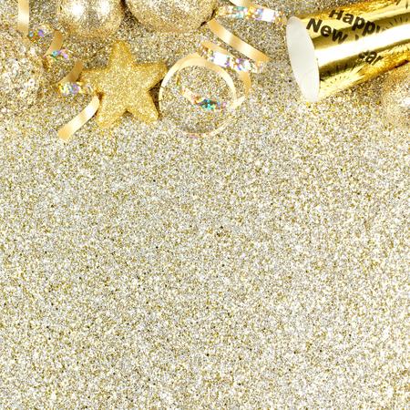 新しい年の前夜の吹流しおよびキラキラ金背景の上の装飾の上枠