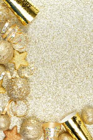 color of year: New Years Eve corner border of streamers and decorations over a glittery gold background Stock Photo