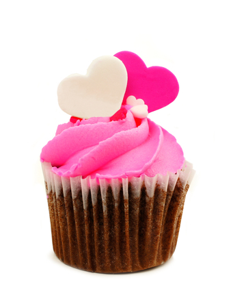 Chocolate Valentines Day cupcake with pink frosting and heart toppers isolated on white photo