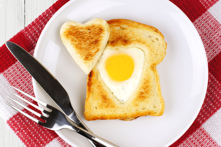 egg white: Heart shaped egg in toast for Valentines Day on white plate with red and white checked cloth Stock Photo