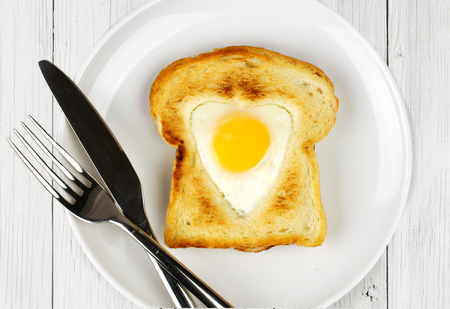 shaped: Heart shaped egg in toast for Valentines Day on white plate with white wood background
