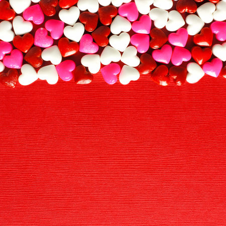 red square: Valentines Day candy top border on a red paper background