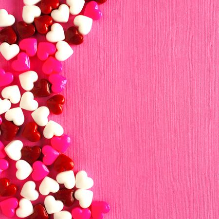 Caramelo Día de San Valentín se curvó borde sobre un fondo de papel de color rosa Foto de archivo - 35065721