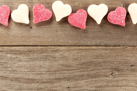 Heart shaped Valentines Day candy top border on a wooden background photo