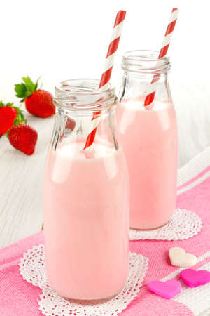 flavoured: Strawberry milk in bottles with pink cloth and hearts on white wood table