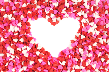Heart shape within Valentines Day candy heart background of sprinkles