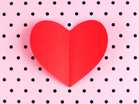 polka dot background: Red paper Valentines Day heart against a pink polka dot background