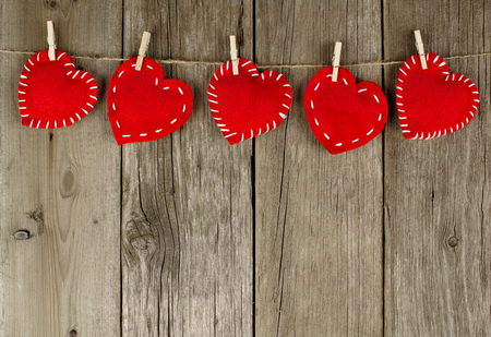 clothesline: Group of Valentines Day cloth hearts with clothespins hanging on old wood background Stock Photo