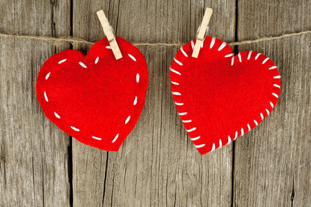 Two Valentines Day cloth hearts with clothespins against an old wood background photo
