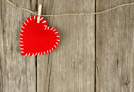 Valentines Day cloth heart with clothespin hanging against an old wood background photo