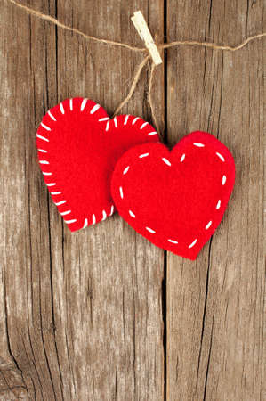 Two Valentines Day cloth hearts with clothespins hanging against an old wood background photo