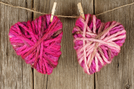 Two Valentines Day wool hearts on clothesline against an old wood background photo