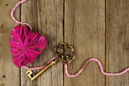 old keys: Valentines Day background with wool heart and key on old wood