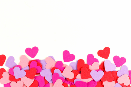 scattered in heart shaped: Valentines Day border of colorful paper hearts over white