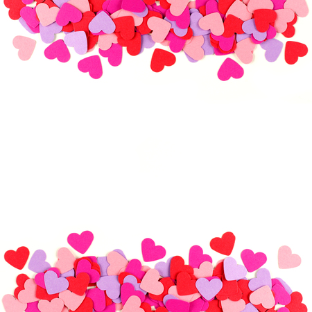 scattered in heart shaped: Valentines Day frame of colorful paper hearts over white
