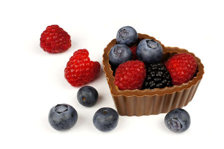 scattered in heart shaped: Heart shaped chocolate cup filled with fresh berries over a white background