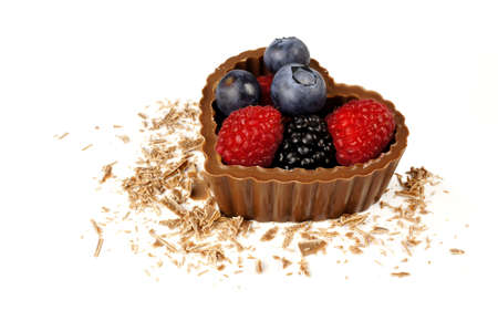 shreds: Heart shaped chocolate cup filled with fresh berries with scattered chocolate shreds over white