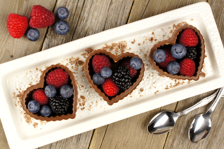 shaped: Heart shaped chocolate cups filled with fresh berries on a plate with wood background