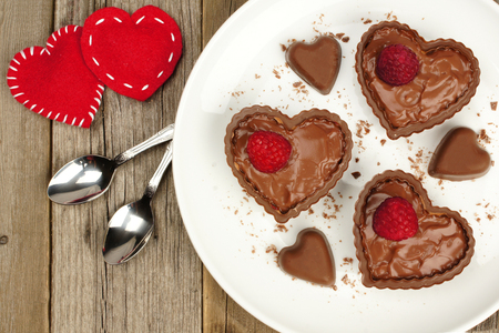 Heart shaped chocolate dessert cups with pudding and raspberries on plate with wood background Stock Photo