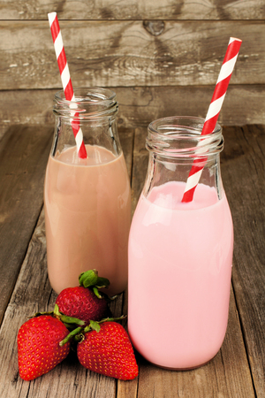 Strawberry and chocolate milk in traditional bottles with straws on old wood background