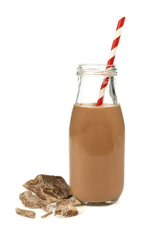 Chocolademelk met stro in traditionele fles met chocolade stukken geïsoleerd op wit