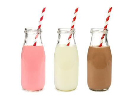 verre de lait: Le lait ordinaire et le chocolat aux fraises dans des bouteilles avec des pailles ray�es isol� sur blanc
