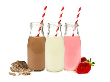 Verschillende smaken melk in flessen met chocolade en aardbeien op wit wordt geïsoleerd Stockfoto