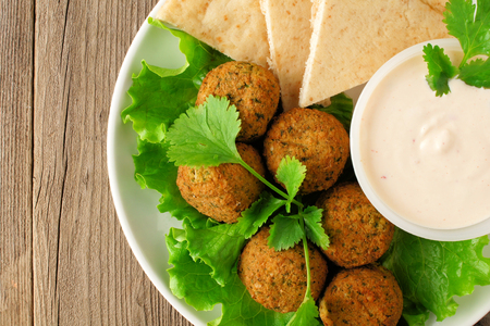 close up food: Plate of falafel with pita bread and tzatziki sauce on wooden table. Close up view from above Stock Photo