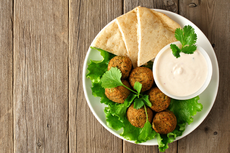 view from the above: Plate of falafel with pita bread and tzatziki sauce on wooden table. View from above